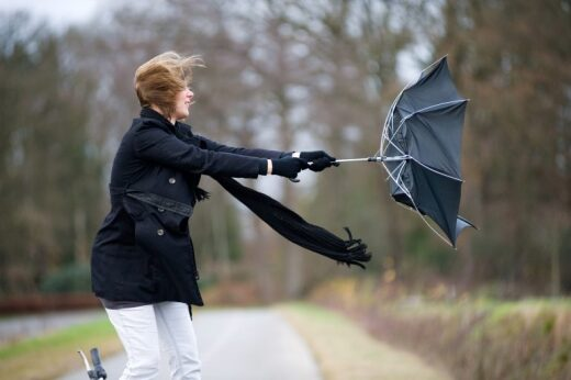 Woman holding umbrella in wind storm